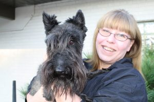 The groomer Carol with a black dog